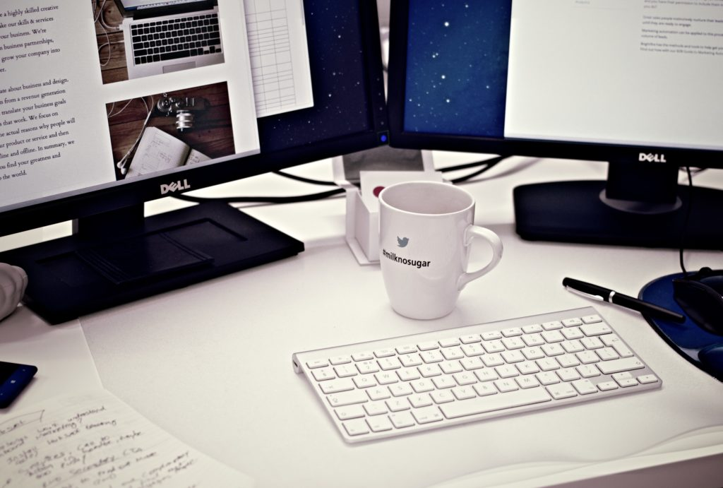 A picture of 2 computer monitors on a desk with a cup of coffee and a keyboard.