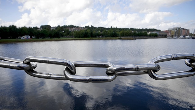A picture of a silver link with a large lake behind it as a metaphor for using internal and external links in a blog post.