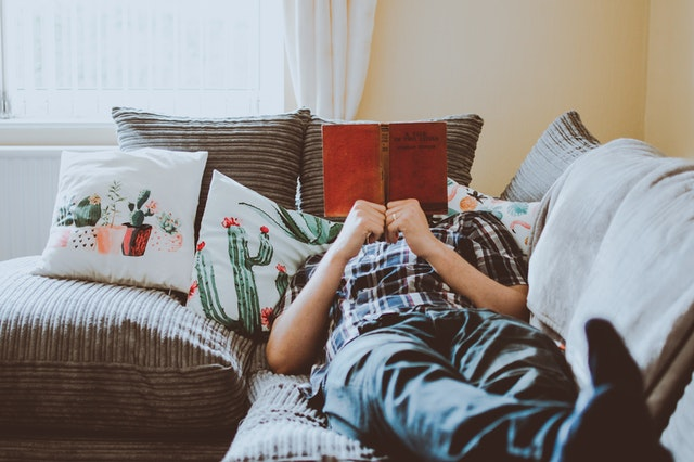 A photo of a guy laying down on a couch while reading a book comfortably.